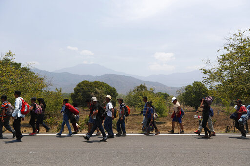 Central American migrants traveling in a caravan to the U.S. walk through Tonala, Chiapas state, Mexico, Sunday, April 21, 2019. The outpouring of aid that once greeted Central American migrants as they trekked in caravans through southern Mexico has been drying up, so this group is hungrier, advancing slowly or not at all. (AP Photo/Moises Castillo)